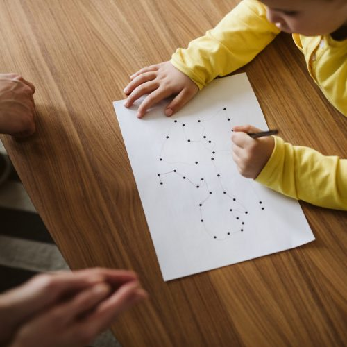 Young boy drawing a picture connecting dots on a psychotherapy session